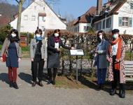 Eine Gruppe von förmlich gekleideten Aktivist:innen stehen an einer Infotafel und präsentieren diese.
