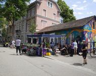 Vor dem kleinen, bunten Haus der Gartenstraße19 steht ein blauer Pavillon und Menschen stehen herum. oder sitzen. Eine Person spricht in ein Mikrofon.