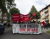 """Demofront mit weißem Transparent auf dem in schwarz-roten Buchstaben steht: """"Kein Angriff ohne Antwort"""""""
