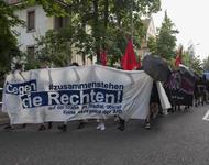 """Ein Demoblock mit einem weißen Fronttransparent. Auf dem steht in blauen Buchstaben: """"Zusammenstehen gegen die Rechten!"""""""