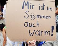 """Ein Pappschild auf dem steht: """"Mir ist im Sommer auch warm!"""" Das """"o"""" ist als sonne gemalt."""