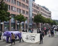 Ein Demonstrationszug mit als Zombies verkleideten bewegt sich in der Basler Str. Vorne weg ein lila Rhino.