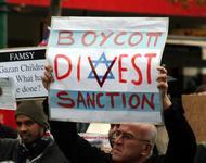 Ein Demonstrant hält ein Plakat in die Höhe, auf dem über die Fahne Israels in roten Lettern steht: Boycott - Divest - Sanction