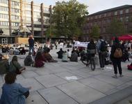 Demonstrierende stehen und sitzen auf dem Platz der Alten Synagoge und hören einer Rednerin zu.