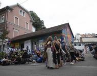 Mehrere Dutzend Menschen stehen vor dem bunten Häuschen in der Gartenstraße 19 und halten eine Kundgebung ab.