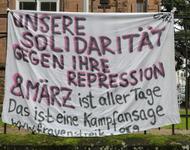 Ein Transparent hängt an einem Geländer, darunter steht ein rot-weißes Megafon. Auf dem Transparent steht: Unsere Solidarität gegen ihre Repression - 8. März ist aller Tage. Das ist eine Kampfansage (www.frauenstreik.org)
