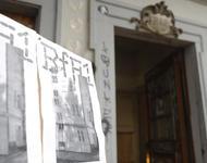 Ein Schild mit Veranstaltungsplakaten der Biennale für Freiburg 1 vor dem Eingang ins historische Klohäuschen.