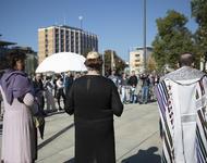 Die drei Redner*innen stehen vor einer Menschenmenge. Rückenansicht.