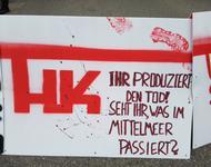 """Ein weißes Schild mit symbolischen Blutflecken & mit roter Farbe steht geschrieben: """"HK - Ihr produziert den Tod! Seht ihr, was im Mittelmeer passiert?"""""""