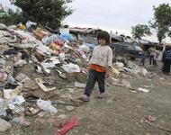 Kleinkind vor Müllberg neben informeller Siedlung 2013 in Serbien - Aber Roma-MigrantInnen treffen auch in Frankreich auf Diskriminierung und schlechte Lebensbedingungen
